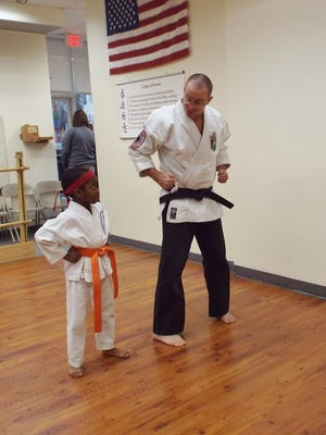 Trey Patterson, 6, of Hyde Park is instructed in isshin-ryu karate, a traditional Okinawan martial arts style, by Steven J. Borland, head instructor and owner of Traditional Okinawan Karate of Pleasant Valley. Borland and his wife, Meghan Borland, offer classes for children through adults five days a week at the Pleasant Valley dojo, including evenings and Saturdays.