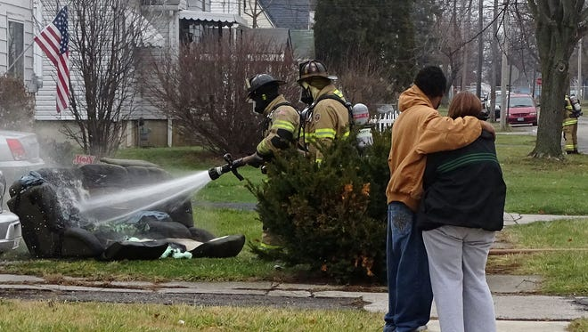 A couple watches as firefighters douse a sofa outside 531 Park Street just before noon on Dec. 17, 2014. Investigators believe a fire in the home was started when an electronic cigarette was plugged into a cellphone charger, causing it to overheat. Nick Bechtel/The Marion Star