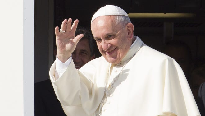 Pope Francis waves to reporters at Rome's Fiumicino international airport, Saturday, Sept. 19, 2015, as he boards his flight to La Habana, Cuba, where he will start a 10-day trip including the United States.