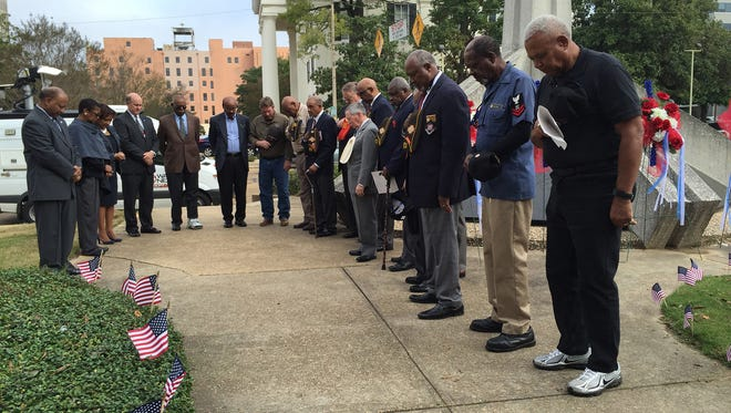 Officials and veterans bow their heads during prayer at the Hinds County Board of Supervisors 2015 Veterans Day Wreath Laying Ceremony. Several chain restaurants in the Jackson metro area are offering discounts or free meals for veterans on Veterans Day 2018.