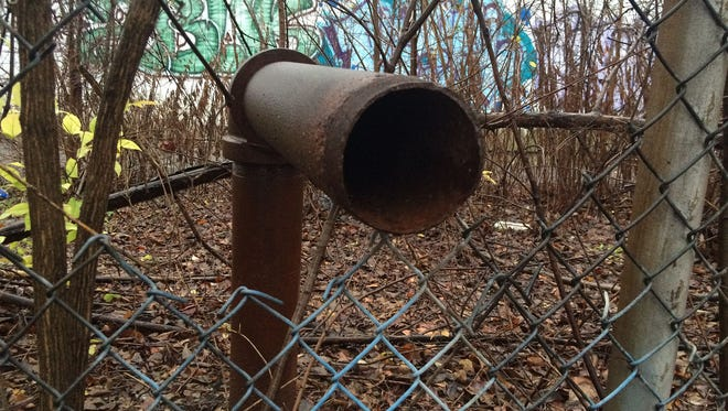 A rusted vent pipe extends through an opening in the fence that surrounds the polluted Black Leaf property in the Park Hill neighborhood of Louisville.