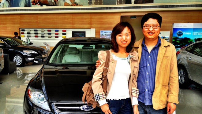 Juan Lu and her husband Jun Gao pick up their first new car, a Ford Mondeo, in this 2012 file photo
