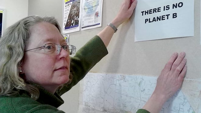 Karen Feather, director of Lebanon Valley College's  Center for Municipal and Corporate Sustainability, hangs a sign in her office recently. The center, which opened in June 2015, received a $4,450 grant from the Center for Watershed Protection Inc. to identify and reduce water pollution in Lebanon County.