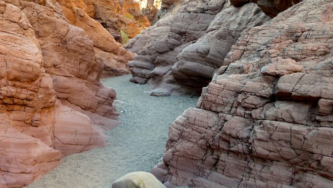 The trail to Crack-in-the-Mountain follows a sandy wash for a mile  then bends left as rocky walls close in around you.
