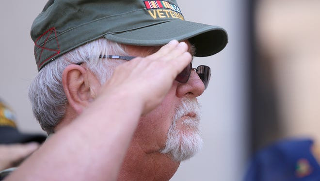 Ronnie Butler salutes while taps is played during a Commemoration of the 50th Anniversary of the Vietnam War on Tuesday in front of the Madison County Courthouse.