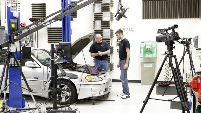 Mark Hicks and Mike Becker work in Wells Vehicle Electronics' studio, where the live web broadcasts are filmed. The Fond du Lac company has more than 10 million views of their videos on YouTube.