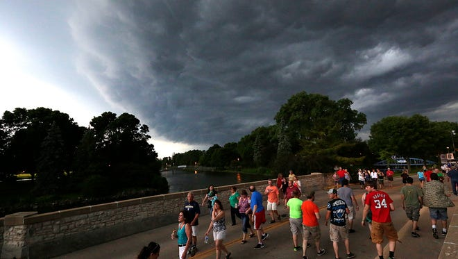 A shelf cloud associated with an approaching thunderstorm looms over Walleye Weekend festival goers Friday evening June 10, 2016.
