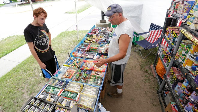 Adrian Cullinan of Fond du Lac shopped last Thursday at Richard Hernandez's fireworks stand outside Philly's on 4th. The city of Fond du Lac allows only certain types of fireworks to be sold by stands and lit by residents.