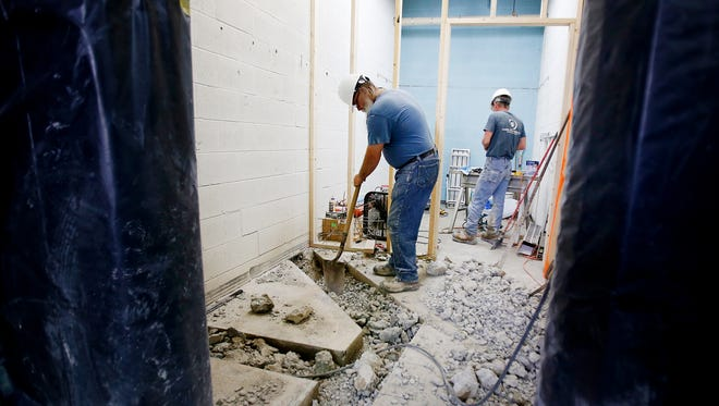 Construction crews work to make a bathroom wheelchair accessible on Wednesday at the new AIM Independent Living Center building, 350 W. Church St., Elmira.