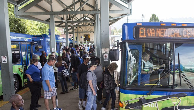 People board buses at the ART Station, or Asheville Transit Center, on Coxe Avenue downtown in 2014.