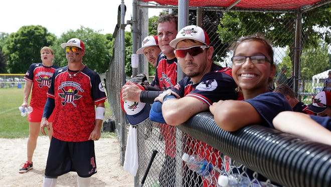 Members of the Wounded Warrior Amputee Softball team watch from the dug out as they take on the Fond du Lac Fire Department Aug. 13 in Lakeside Park.
