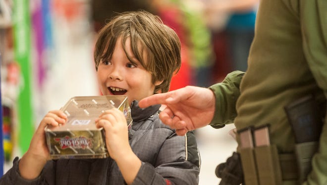 Dell Petersen, 7, grins at the thought of playing with the Yu-Gi-Oh game he chose during Shop with a Cop at Target Tuesday, Dec. 13, 2016.