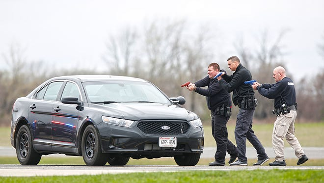 Three Fond du Lac County Sheriff's deputies approach a car with their guns drawn as part of a yearly training exercise at the Fond du Lac County Airport. The training focuses on vehicle pursuits and the risks associated with them as well as high risk traffic stops.