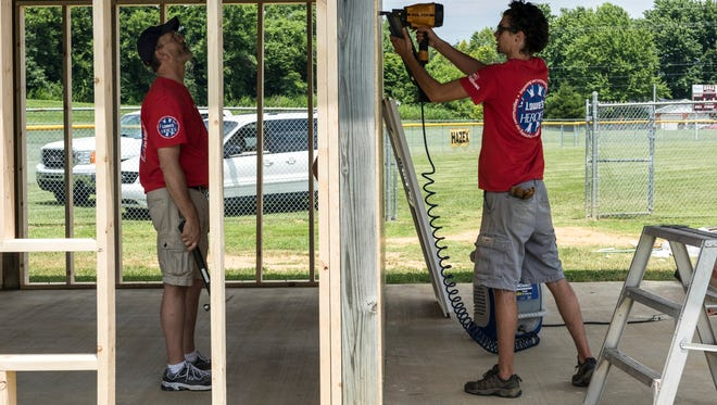 Ronnie Shelton (left) oversees Brandon Agnew (right) as he uses a nail gun to build a 20x20 softball facility room, which will be used for game officials and meetings at Newman Softball fields in Henderson on Tuesday.