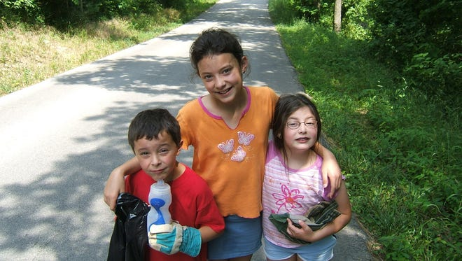 Nathan, Samantha and Jenna Groves, from left, stand on Triple M in Christian County, just before a June 3, 2005, outing to clean up the country road.