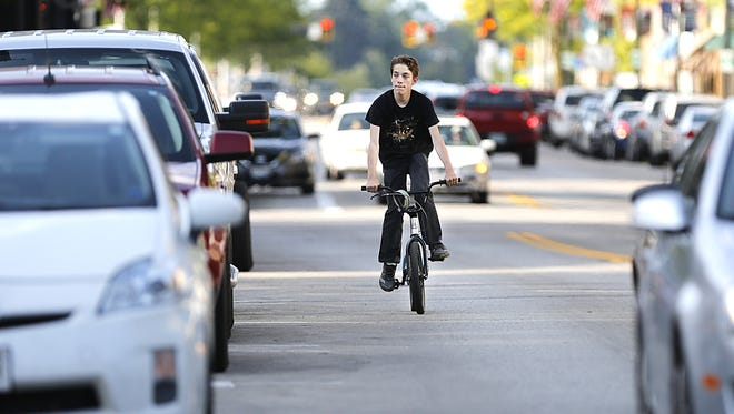 Andrew Allen of Fond du Lac rides his bike Friday on Main Street in Fond du Lac.