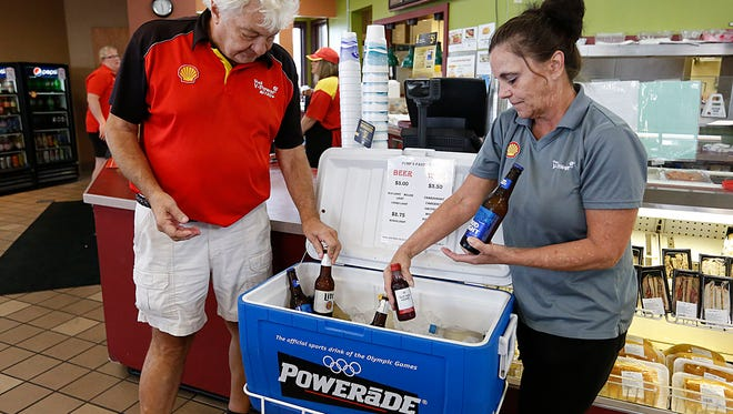Bob and Lois LeMense stock a cooler with beer and wine Wednesday to be bought and consumed with meals sold in the restaurant portion of their gas station, Pump N Pantry, at the intersection of Pioneer Road and Hickory Street.