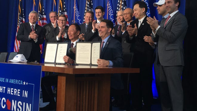 Foxconn chair Terry Gou (left) and Gov. Scott Walker show the signed agreement that officially commits Foxconn to building a plant in Wisconsin.
