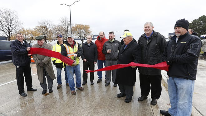 Representatives from the Wisconsin Department of Transportation, Mercury Marine and local government officials take part in a ribbon cutting ceremony Wednesday for the re-done portion of Pioneer Road, from Military Road to Hickory Street. Improvements included a roundabout added to the intersection of Pioneer and Military as well as stop and go lights at an employee entrance to Mercury Marine.
