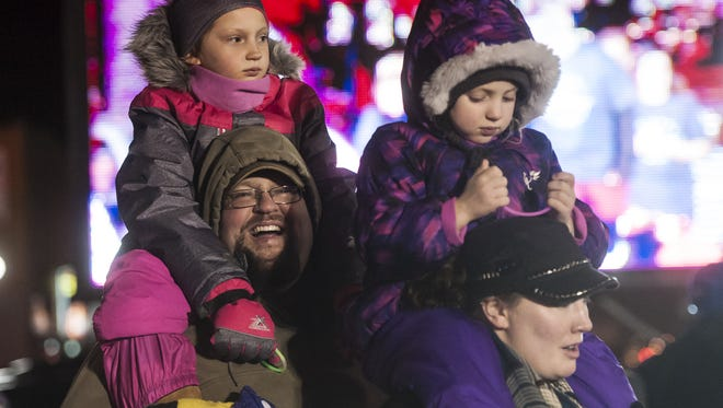 Left to right, Justin and Kari Maki carry Aili, 3, and Madison, 7, on their shoulders as they watch the Polar Plunge during last year's Christmas Stroll.