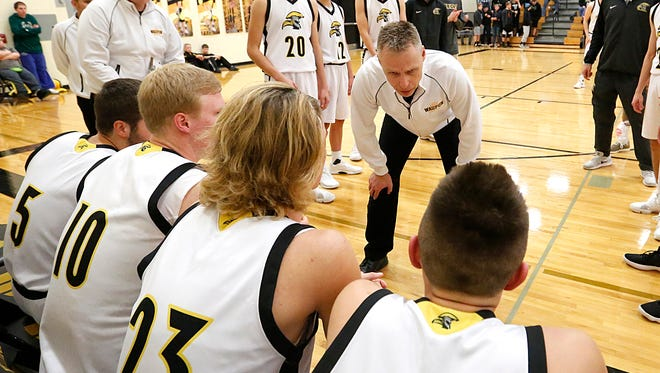 Waupun boys basketball coach Dan Domask talks to his team before their game against Valders on Friday.