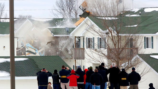 Federal and local law enforcement personnel watch as explosives found in an apartment building in Beaver Dam are detonated Wednesday. The explosives were found after a previous explosion killed the apartment's tenant Monday.