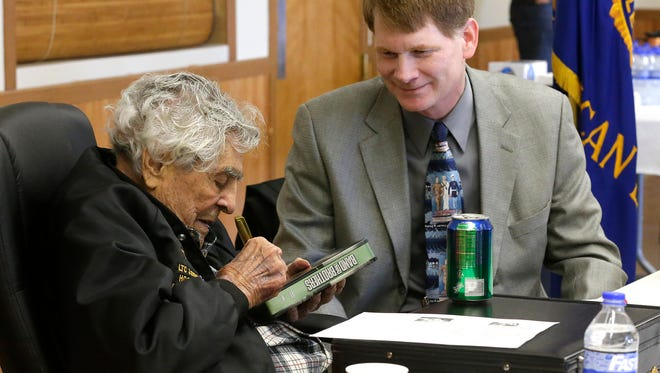 """Decorated WWII hero and Fond du Lac native James """"Maggie"""" Megellas signs a copy of """"Band of Brothers"""" for Assembly Rep. Jeremy Thiesfeldt (R-Fond du Lac) Saturday at the war hero's 101st birthday celebration. A steady stream of visitors, including government leaders, stopped in to say hello at the American Legion Post #75  in Fond du Lac."""