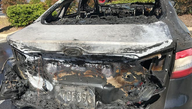 A glass repairman used an open flame to try to fix this Ford Fusion's windshield Tuesday, March 27, 2018, in Redding, Calif. The car caught on fire and the flames spread to the car next to it.