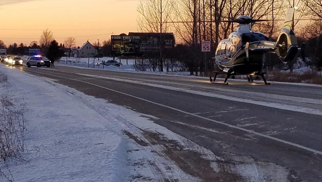 Eagle III medical helicopter is seen on Highway 22 as Oconto County Deputy Nick School holds traffic to create a landing zone in a Feb. 5 incident in the town of Oconto Falls.
