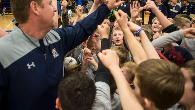 Montana State head coach Jeff Choate leads a huddle with kids during the Triangle Classic Football Camp with the Montana State University team last spring at Great Falls High's Swarthout Fieldhouse.