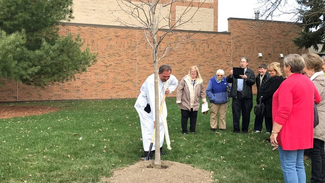 The Rev. Stan Tokarski helping plant a tree outside St. Joseph Catholic Church in South Lyon.