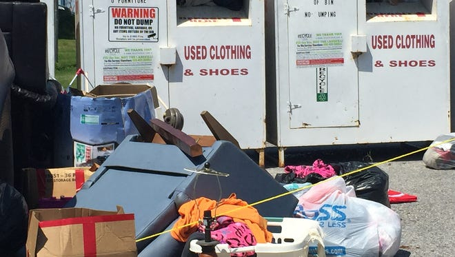 Discarded furniture and other items are scattered in front of clothing collection bins in the 800 block of Lincoln Way West, Chambersburg, today. Many residents are annoyed by the dumping.