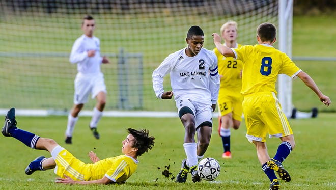 DeJuan Jones, 2, of East Lansing works his way past Haslett defenders Brian Coscarelli ,left, and a teammate during their Division 2 District semifinal game Wednesday October 15, 2014 in St. Johns.  KEVIN W. FOWLER PHOTO