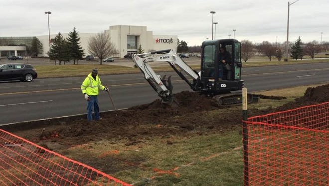 Workers start construction on a concrete pad for a Regional Transit Service bus shelter on Hylan Drive in Henrietta.