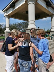 Fishers women pray with April Meyer (foreground), wife of an Indianapolis Metropolitan Police Department officer, following a prayer vigil Friday, Sept. 4, 2015, outside the Fishers Police Department.