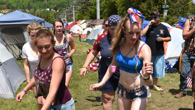 Meghan Arnolds, right, 21, of Wappingers Falls, and Ashley Mazzei, left, 21, of New Paltz, lead a group in line dancing at the 2017 Taste of Country Music Festival on Hunter Mountain.
