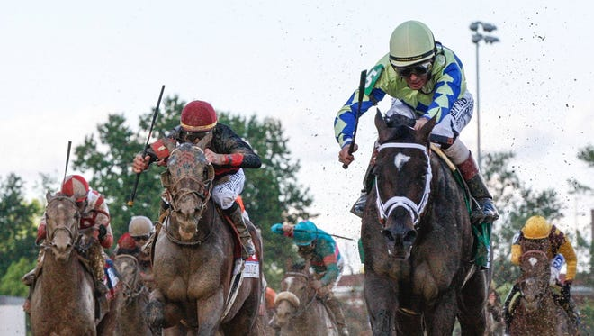 Always Dreaming rides to victory in the 143rd Kentucky Derby in the mud at Churchill Downs.