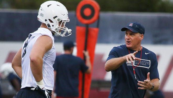 Head coach Rich Rodriguez works with Arizona tight end Trevor Wood during practice.
