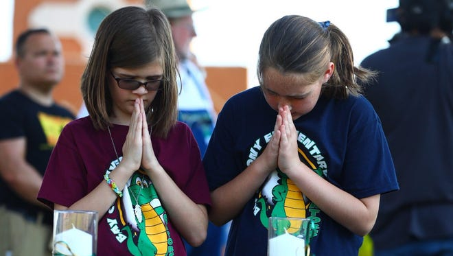 People wait for the start of a vigil in Santa Fe, Texas following a shooting that killed 10 at Santa Fe High School on Friday morning.