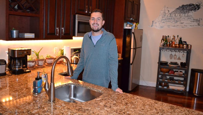 Josh Myers stands in the kitchen of his condo on Salisbury's Downtown Plaza that he rents out through Airbnb.