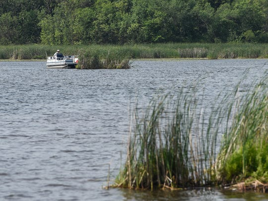 A pontoon boat is used to nudge a floating bog on Linneman