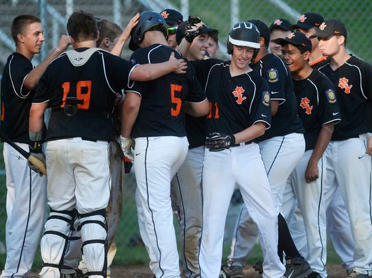 Brendon Delridge is greeted by his Suburban York American Legion teammates after he hit the game-winning home run during a game against Hanover in June.