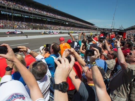 Fans watch and photograph the start of the Indianapolis 500 at the Indianapolis Motor Speedway, May 25, 2014.
