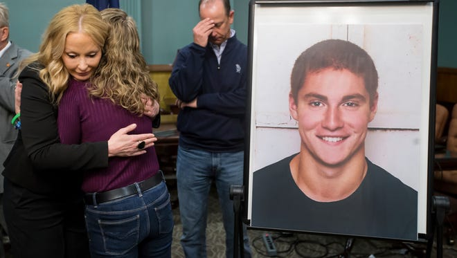 Centre County District Attorney Stacy Parks Miller, left, hugs Evelyn Piazza as her husband, Jim, stands in the background after announcing the findings in the investigation of the February death of the couple's son, Timothy Piazza, seen in photo at right, at Penn State University's fraternity Beta Theta Pi.