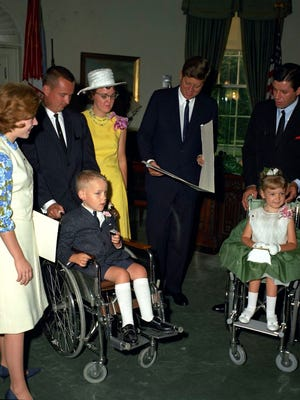 President John F. Kennedy (center) reads an illuminated scroll from the Muscular Dystrophy Associations of America, Inc. (MDAA), presented by National Youth Chairman for the MDAA, actress Patty Duke in the Oval Office at the White House. National Poster Children for the MDAA, Robbie and Kerrie Whitaker, sit in front. Back row (L-R) Ms. Duke; Robbie and Kerrie's parents, C. Leigh and Joyce Whitaker; President Kennedy; and National Chairman for the MDAA, comedian Jerry Lewis.
