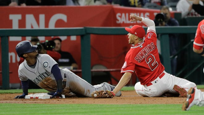 Los Angeles Angels' shortstop Andrelton Simmons (right) looks at third-base umpire Greg Gibson after applying a tag on the Mariners' Jean Segura during the third inning Saturday. Segura was called out after a video review.