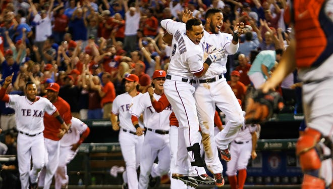 Elvis Andrus and  Leonys Martin celebrate Jurickson Profar's walkoff home run that kept the Rangers close in the AL playoff race.