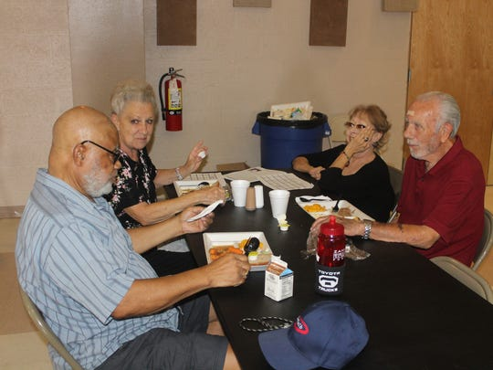 From left to right, Charles Cromer, Bonnie Wright, a woman who preferred not to give her name, and Dale Wright enjoy a meal together at the Sgt. Willie Estrada Memorial Civic Center on Wednesday afternoon.