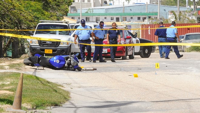 Yellow crime scene tape stretches across Finegayen Road and a motorcycle could be seen lying on the ground as Guam Police officers conduct an investigation of a shooting in Harmon on Wednesday, June 15.