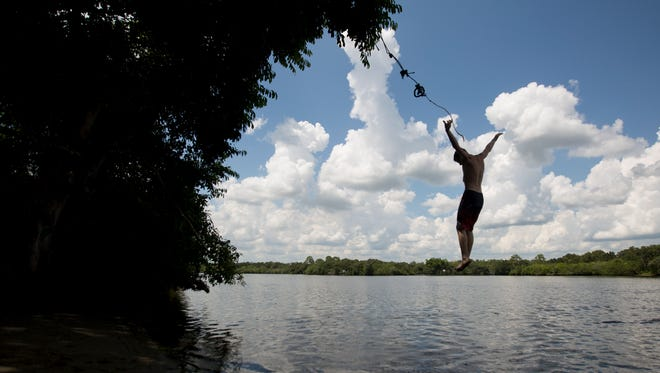 Jalen Pledger,16, A student at Riverdale High School enjoys a rope swing on the Caloosahatchee River in Olga in August of this year. The river has long been a source of recreation.